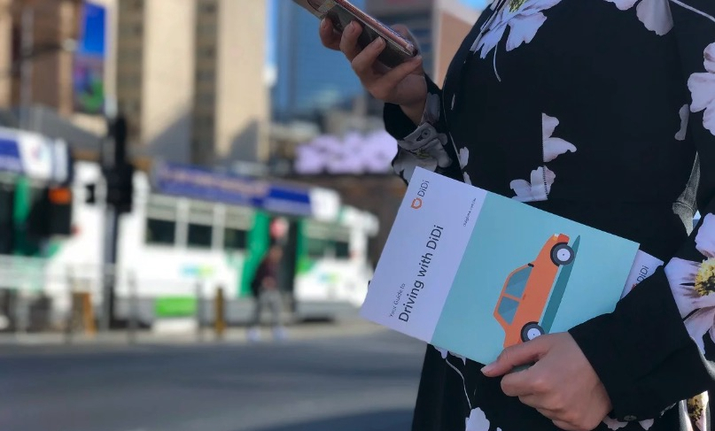 """A woman holds a """"Driving with Didi"""" pamphlet. /Photo courtesy of Technode"""
